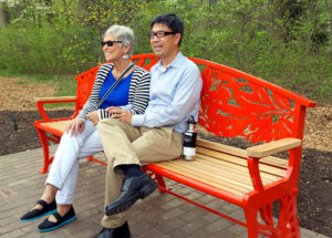"""Artist Linda DePalma with major donor Derrick Chin on her """"Sassy Bench"""""""
