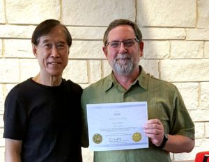 Peter receiving Sheng Zhen teaching certification from Master Li