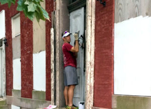 Andrew Parlock painting a building across from the lot